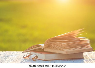 Close up book and eye glasses on wooden table with abstract blur and bokeh in sunrise or sunset time