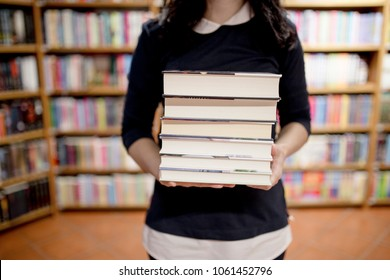 Close up of book stack in hands of a young girl in the library.