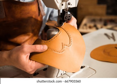 Close up of a bootmaker working with leather textile on sewing machine at workshop