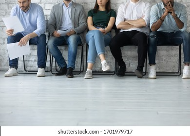 Close up of bored diverse multiracial job candidates sit in queue line feel anxious wait for interview, stressed multiethnic applicants get ready for work recruitment talk, employment concept