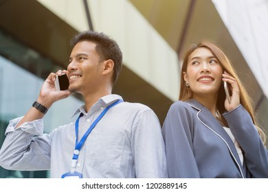 close up both of young businesspeople holding smartphone and talking at outside building office, business telecommunication concept