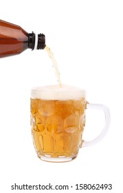Close up of bottle of beer pouring into a mug.