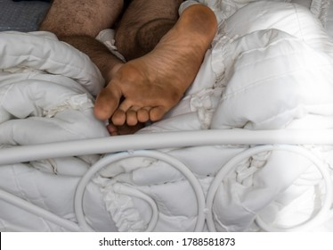 close up of the bottom of a bare dirty male caucasian foot on a white bed comforter white scroll metal bed