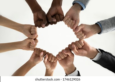 Close up bottom view diverse employees team holding fists in circle, expressing unity and power in teamwork, multiethnic business people engaged in team building activity at briefing