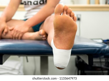 Close up bottom view of a female athlete's foot in an ankle tape job from the bottom of a table