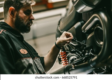 Close up bottom view of the handsome motorcycle mechanic checks the oil level in the motorcycle. The sports bike is on the lift.