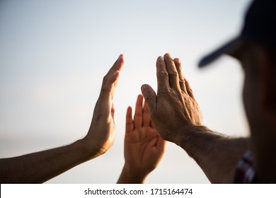 Close up bottom view of people giving hand showing unity and teamwork. Friendship happiness leisure partnership team concept.