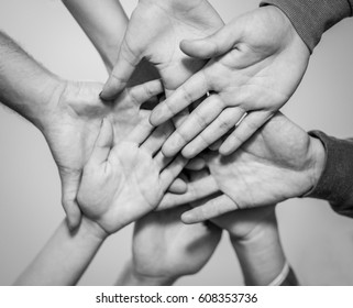Close up bottom view of young people putting their hands together - Friends with stack of hands showing unity and teamwork - Focus on top right hand - Black and white editing - Warm contrast filter