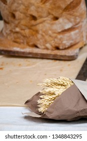 Close up of bouquet of golden wheat ears wrapped in craft paper and loaf of freshly baked traditional rustic whole grain bread on cutting board in background