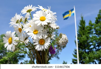 A close up of a bouquet of midsummer flowers with a Swedish flag blowing in the background.