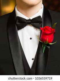 Close up of boutonniere and bow tie for senior prom. Teenage boy wears tuxedo.