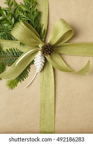 Close up of bow and natural decorations on Christmas gift. Christmas present wrapped in recycled wrapping paper.