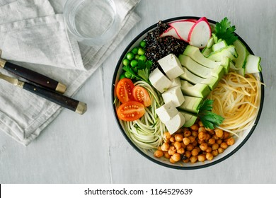 Close up bowl of buddha with spiralized vegetables on white wooden table with border, top view. Healthy food clean eating