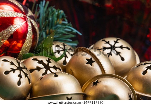 close up of a bowl full of golden jingle bells with a snowflake pattern and a red with gold glitter ball ornament in selective focus with copy space