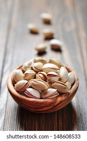 close up of a bowl of pistachio nuts over wooden background