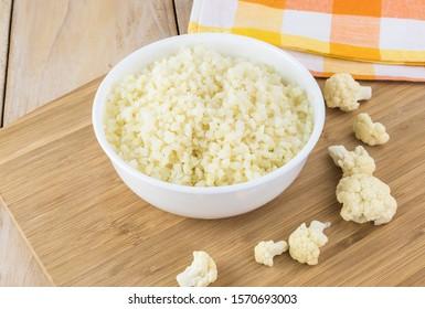 Close up of bowl with raw cauliflower rice.