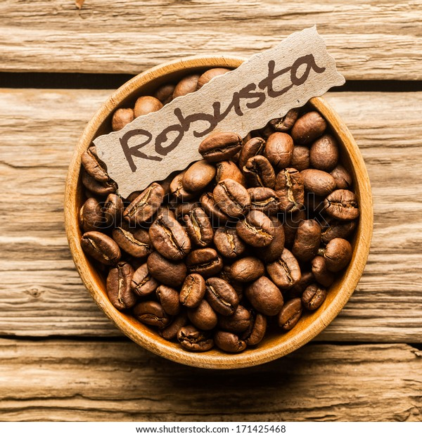 Close up of a bowl of Robusta coffee beans over an old wooden table