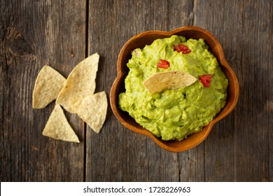 Close up of a bowl of traditional mexican guacamole with nachos chips on a wooden background