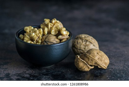 A close up of a bowl of walnuts on a dark rustic surface