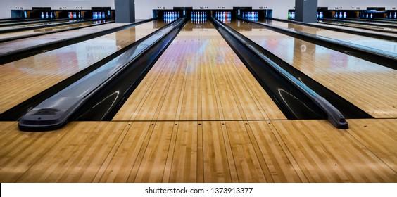 Close up of bowling balls, bowling pins bowling balls in a row.