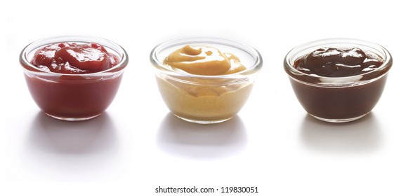 close up of bowls of tomato ketchup and mustard and barbecue sauce