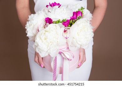 close up of box with peony flowers in female hands over beige background