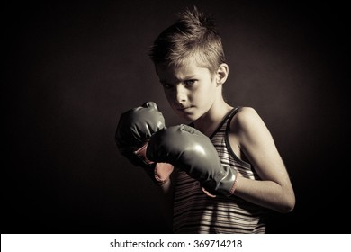 Close up Boxer Boy Wearing Hand Gloves and Looking Fierce at the Camera Against Black Background.