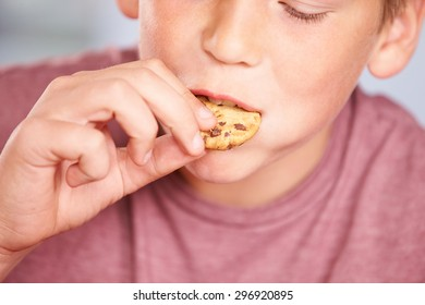 Close Up Of Boy Eating Chocolate Chip Cookie