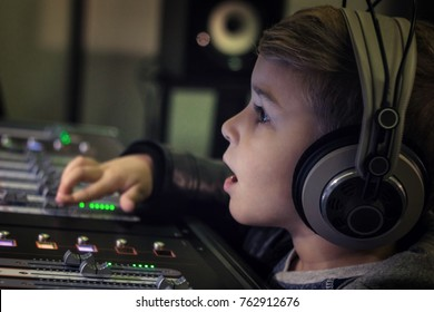 Close up of boy with headphones adjusting volume on electronic sound mixer in recording studio.