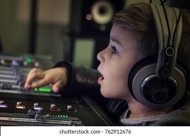 Nahaufnahme eines Jungen mit Kopfhörern, der Lautstärke auf den elektronischen Tonmischer im Aufnahmestudio eingestellt hat.