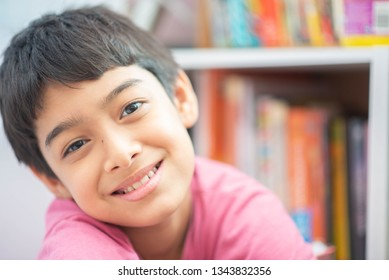 Close up boy in the library with full of books