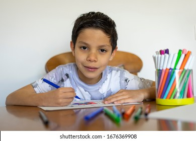 Close up of boy painting a mandala with his colored markers