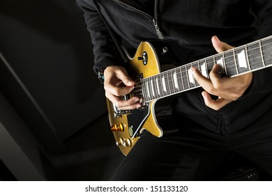 Close up of a boy playing a electric guitar.