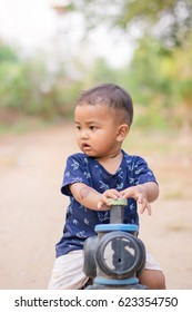 close up boy playing on the motorcycle in the park . child driving motorcycle toy,happiness boy with toy , sad boy , crying boy  with copy space