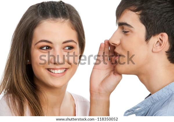 Close up of boy whispering to cute girl.Isolated on white.