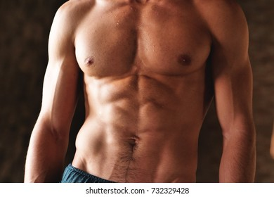 Close up of a boy's muscles after finishing the workout and notice sculpted abdominal and pectoral abdomen. Concept of: supplements, power, workout, workout