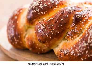 Close up of braided challah bread with sesame and poppy seeds.