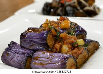 Close up braised eggplant on white dish inside Chinese restaurant