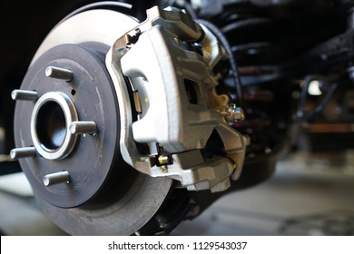 Close up of Brake Disc of the vehicle for repair.Automobile mechanic in process of new tire replacement.Car brake repairing in garage.Car Service and technician concept.