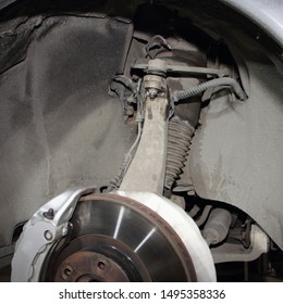 Close up brake disk with caliper, steering rod and arm of car pneumatic suspension and air cylinder - modern transmission repair