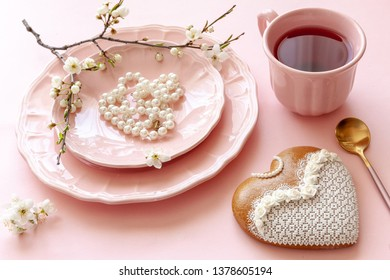 Close up of Branch of blossoming cherry cup of tea, pearl necklace, gingerbread on pastel candy pink background