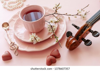 Close up of Branch of blossoming cherry cup of tea, pearl necklace, gingerbread  and violin on pastel candy pink background