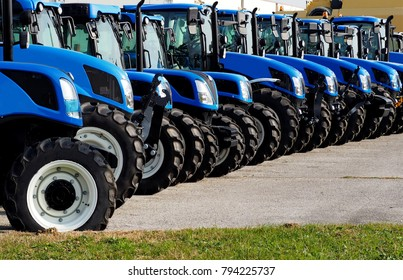 Close up of brand new blue tractors,  side by side, in a long line