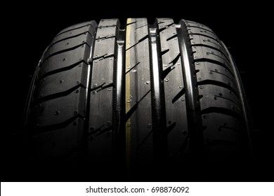 Close up of the brand new summer tire with modern tread on a black background