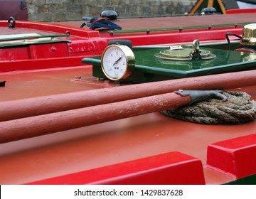 a close up of a brass gauge porthole boathooks and ropes on an old red canal narrow boat