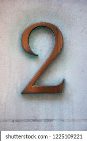 A Close Up of a Brass Number Two Door Number on a Wall