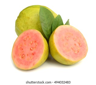 A close up of a brazilian guava cut in a half in front of some entire guavas.