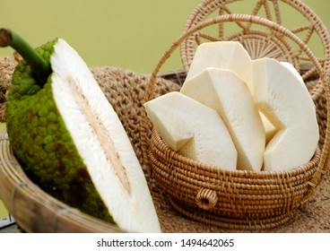 Close up breadfruit cut in half and slice in handmade basket on yellow background