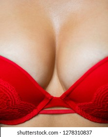 Close up of breast of girl presenting her bra. Red bra. Sexy boob. Woman with big natural sexy boobs in lingerie. Closeup of sexy female boob in red bra. Plastic surgery. Sensual girl.
