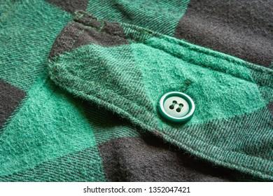 Close up of breast pocket on green black vintage flannel plaid shirt